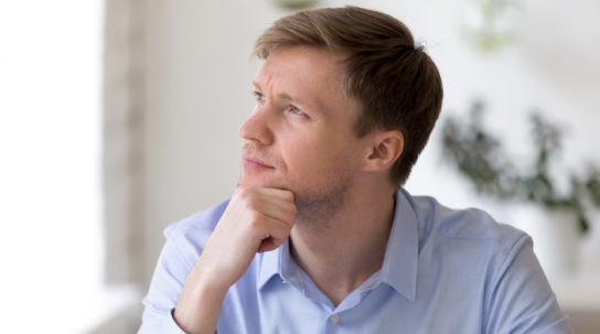 Contemplating serious man sitting at workplace looking away thinking making important decision analysing results feels doubts and unsure. Concentrated businessman tired take a break distract from work